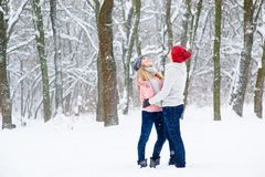 Young couple in winter forest. Beautiful couple in knitted hats catch snowflakes outdoors Stock Image