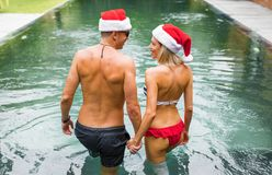 Couple on winter holidays going for a swim in the pool. Young couple on winter holidays going for a swim in the pool Stock Images
