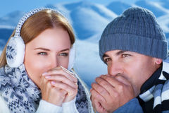 Young couple in the winter park. Closeup portrait of beautiful young couple try to warming up their hands, spending winter holidays in the snowy mountains Royalty Free Stock Photo