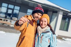 Winter vacation. Young couple standing together outdoors with keys from new house close-up smiling cheerful blurred royalty free stock image