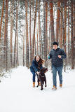 Young Couple With A Dog Having Fun In Winter Stock Photo