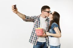 Young couple, woman and man in 3d glasses watching movie film on date, holding bucket of popcorn and cup of soda or cola royalty free stock photos