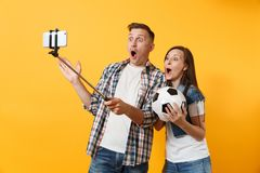 Young couple, woman man, football fans doing selfie on mobile phone with monopod selfish stick, cheer up support team. Young couple woman man, football fans royalty free stock photo