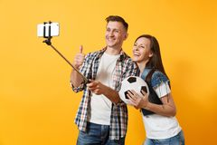 Young couple, woman man, football fans doing selfie on mobile phone with monopod selfish stick, cheer up support team. Young couple woman man, football fans royalty free stock photos