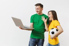 Young couple, woman man, football fans in yellow green t-shirt cheer up support team with soccer ball, watching game on stock photography