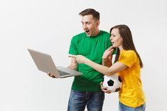 Young couple, woman man, football fans in yellow green t-shirt cheer up support team with soccer ball, watching game on stock photo
