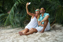 The young couple, the woman and the man sit on the beach and will take the selfies dressed in bright clothes and in sunglasses. Stock Image