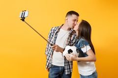 Kiss couple, woman man, football fans doing selfie on mobile phone with monopod selfish stick, cheer up support team stock photo