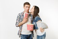 Young couple, woman and man watching movie film on date holding bucket of popcorn plastic cup of soda or cola and bundle. Young couple, women and men watching stock photo