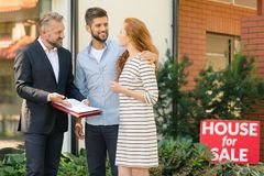 Couple wondering about buying apartment. Young couple wondering about buying apartment while agent presenting sales contract Royalty Free Stock Images