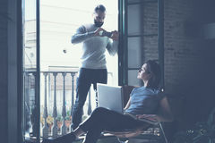 Young couple work together. Bearded man making photo smartphone beautiful girl. Working with new startup project in. Young couple work together. Bearded men stock images