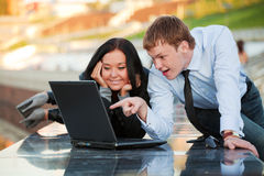 Young business couple using laptop outdoor Royalty Free Stock Images