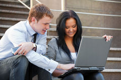 Young business couple using laptop on the steps Royalty Free Stock Photography