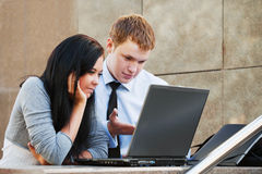 Young couple working on laptop. Against office wall Stock Photos