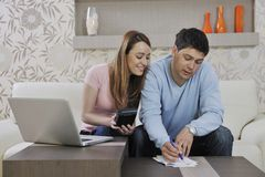 Young couple working on laptop at home Stock Images