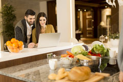 Young couple working on laptop in the kitchen Stock Images