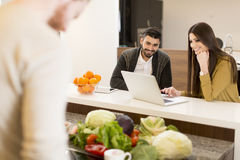 Young couple working on laptop in the kitchen. Couple working on laptop in the kitchen Royalty Free Stock Photos