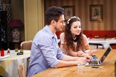 Young couple working on laptop sitting in the kitchen Stock Photo