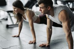 Young couple is working out at gym. Attractive woman and handsome muscular man are training in light modern gym. Doing plank.Push-. Young couple is working out royalty free stock image