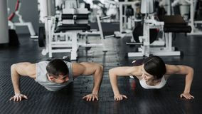 Young couple is working out at gym. Attractive woman and handsome muscular man are training in light modern gym. Pushing up stock image