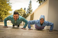 Young couple working pushbuttons on street. Healthy lifestyle. Royalty Free Stock Image