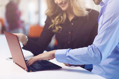 Young couple working together on a laptop in the office. Teamwork concepts. Stock Photography