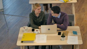 Young couple working together on a laptop in the office. Top view. Professional shot in 4K resolution. 090. You can use it e.g. in your commercial video stock footage