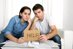 Young couple worried at home in bad financial situation stress. Young couple worried need help in stress at home couch accounting debt bills bank papers expenses Royalty Free Stock Photo