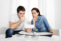 Young couple worried at home in stress accounting bank payments Stock Photos