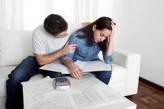 Young couple worried home in stress husband comforting wife in financial problems Stock Images