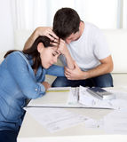 Young couple worried home in stress husband comforting wife in financial problems Stock Image
