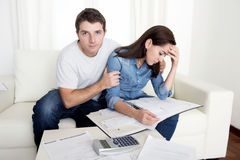 Young couple worried home in stress husband comforting wife in financial problems Royalty Free Stock Images