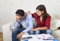 Young couple worried home in stress wife comforting husband accounting debt unpaid bills bank papers expenses. And pending payments feeling desperate in bad royalty free stock image