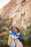 Young couple wrapped in flag of Ukraine are kissing in canyon. Closeup. Young couple wrapped in flag of Ukraine are kissing in canyon against backdrop of palm Royalty Free Stock Photo