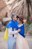 Young couple wrapped in flag of Ukraine are kissing in canyon against backdrop of palm trees and rocks royalty free stock photos