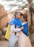 Young couple wrapped in flag of Ukraine are kissing in canyon. Closeup. Young couple wrapped in flag of Ukraine are hugging in canyon against backdrop of palm Stock Image