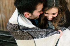 Young couple wrapped in plaid Royalty Free Stock Photography