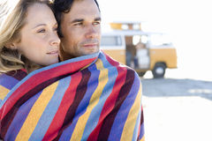Young couple wrapped in towel on beach, camper van in background, close-up Stock Image