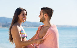 Young couple wrapped in towel on beach Stock Photos