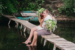 Young couple in a wreath with a bouquet on a wooden bridge laughing Royalty Free Stock Photo