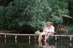 Young couple in a wreath with a bouquet on a wooden bridge laughing Stock Photos