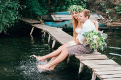 Young couple in a wreath with a bouquet on a wooden bridge laughing Royalty Free Stock Image