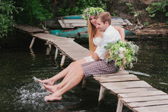 Young couple in a wreath with a bouquet on a wooden bridge laughing Stock Photography