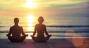 Young couple yoga on the beach during sunset. Relax. Royalty Free Stock Photo