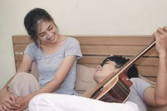 Young couple, young man playing guitar in a relaxing holiday room. stock photo