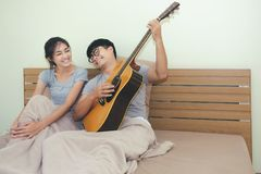 Young couple, young man playing guitar in a relaxing holiday room. stock image
