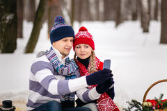 Young couplel looking at phone and taking photos on the snow Royalty Free Stock Photo