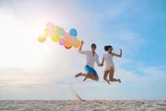 Young Couples Are Jumping, Catching Balloons On The Beach In The Stock Images