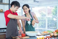 Young Couples Asian. They both look each other`s eyes. Smile, Cooking so fun together in kitchen royalty free stock photos