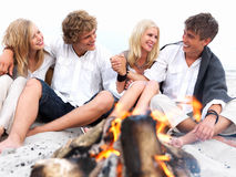 Young couples in casual sitting by bonfire at beac Stock Images